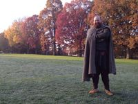 """A figure with a full beard in a wool cloak stands, arms crossed on a frosty lawn. In the background there is a row of oak and maple trees that are in vibrant fall colors."""